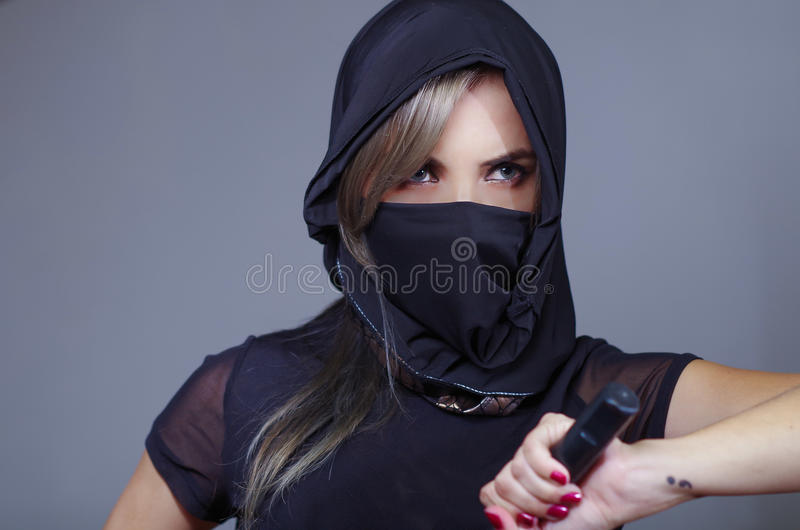 Samurai woman dressed in black with matching veil covering face, holding hand on sword facing camera, ninja concept.  royalty free stock images