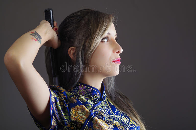 Samurai woman dressed in traditional colorful flower pattern asian silk dress, holding arm over shoulder grabbing sword stock photos