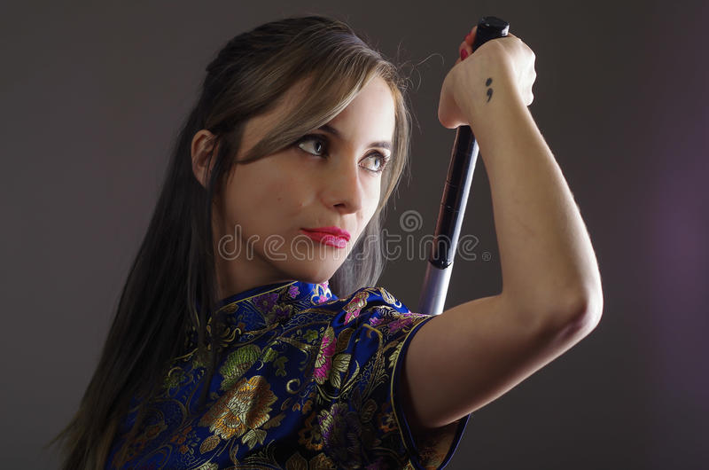 Samurai woman dressed in traditional colorful flower pattern asian silk dress, holding arm over shoulder grabbing sword stock images