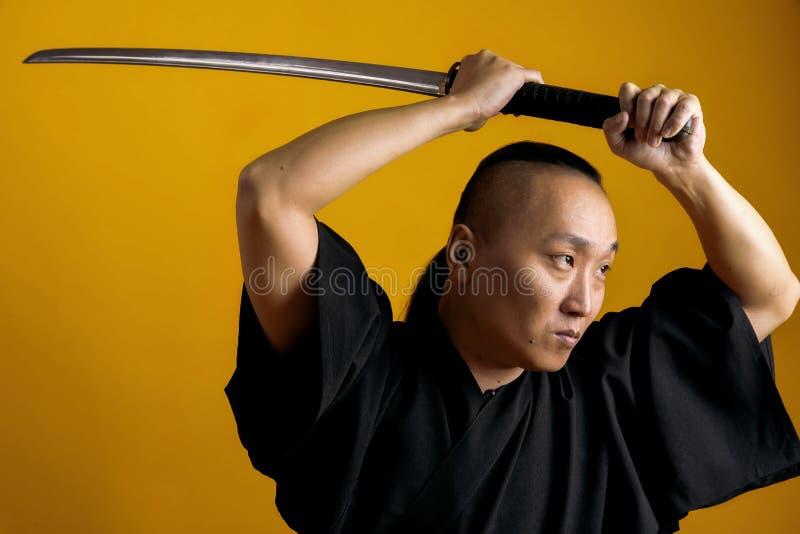 Samurajer i svart kimano lyftte upp hans svärd, på en gul bakgrund royaltyfri foto