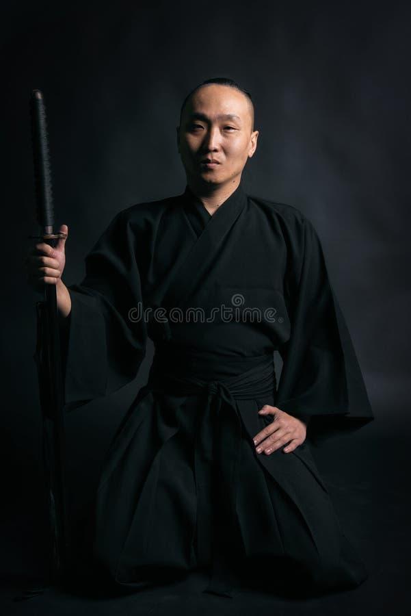 Samurajer i svart kimano med svärdet i händer på en svart bakgrund royaltyfri fotografi