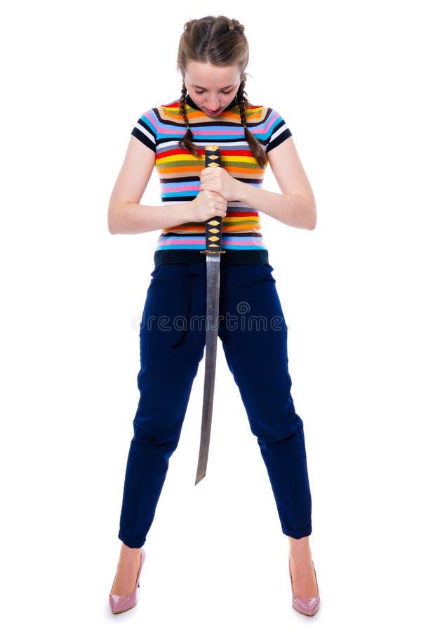 Samurajflickan som rymmer en katana i hennes händer, bugade hennes huvud i hänsyn Isolering på en vit arkivfoto