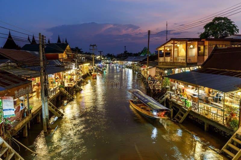 Samut Songkhram/泰国- 2018年4月21日:暮色看法Amphawa市场运河和许多人民作为走的游人,购物, 免版税图库摄影