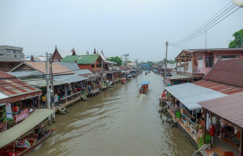 Samut Songkhram/Tailândia - 1º de abril de 2018: Muitos povos como os turistas que andam, comprando ao redor no mercado de flutua fotografia de stock royalty free