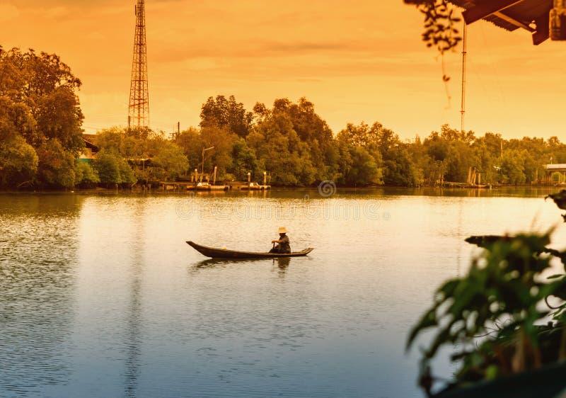 Samuth Songkram, Таиланд 18-ое апреля 2017: Укомплектуйте личным составом грести малую деревянную шлюпку, жизнь вдоль реки стоковое изображение rf