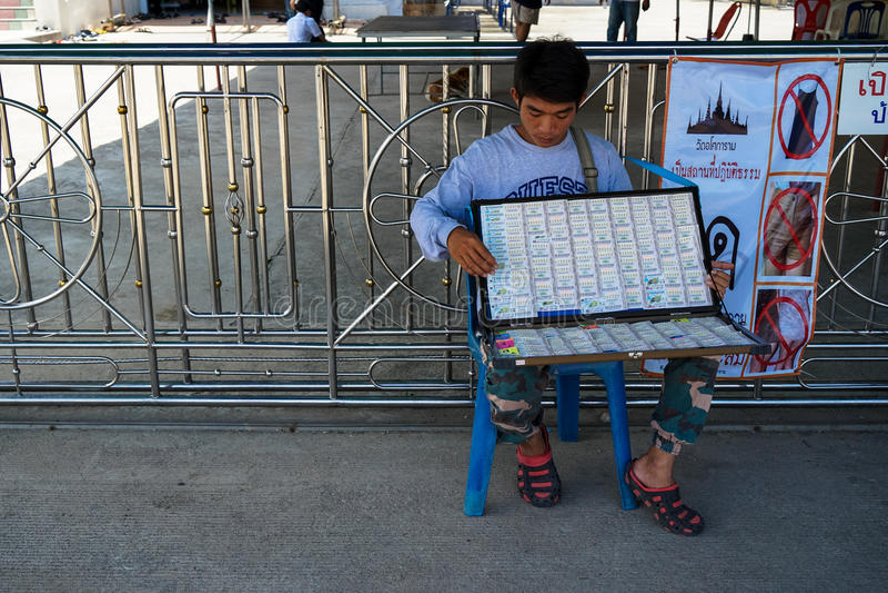 Samutprakarn Tajlandia, Sierpień, - 14, 2017: Niezidentyfikowany sprzedawcy mężczyzna mienia i obsiadania pudełko loteryjni bilet obraz royalty free