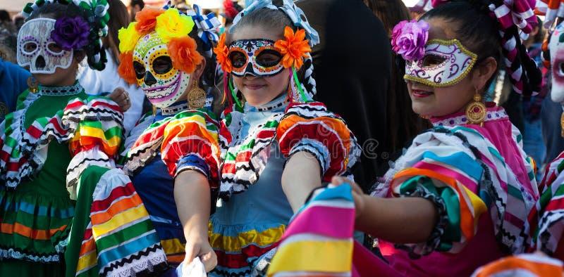 SAN ANTONIO, TEJAS - 28 de octubre de 2017 - muchachas que llevan máscaras coloridas y los trajes tradicionales para Dia de Los M imagen de archivo