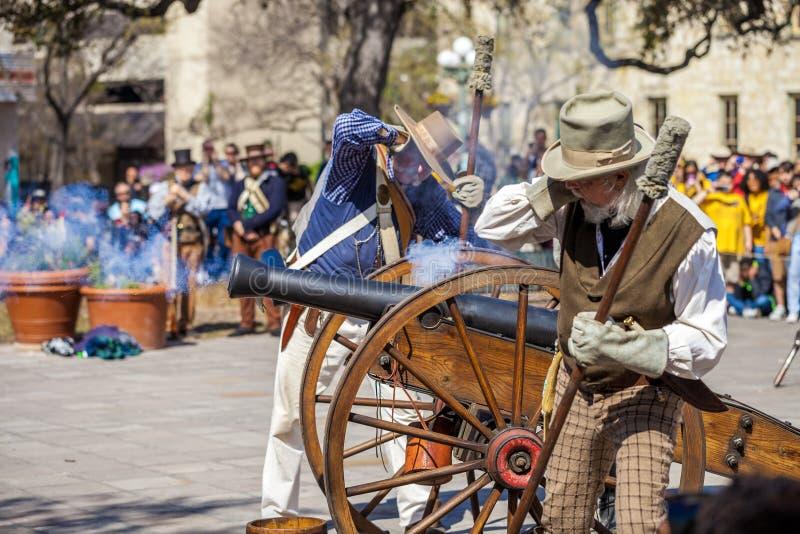 SAN ANTONIO, TEXAS - 2 de março de 2018 - os homens vestidos como soldados do século XIX ateia fogo ao canhão antigo para o reena fotos de stock