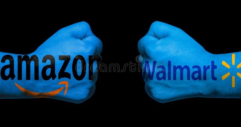 SAN ANTONIO, TX - 9. April 2018 - Amazonas- und Walmart-Logos gemalt auf zwei geballten Fäusten, die einander/Konzept Kleinkriege lizenzfreie stockfotos