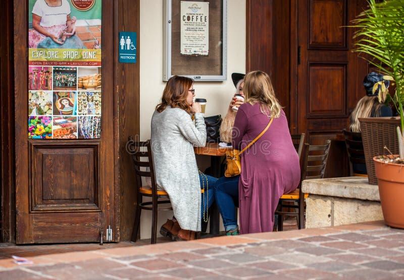 SAN ANTONIO TX - JANUARI 6, 2018 - gruppen av tre kvinnor sitter på ett litet tabell- och drinkkaffe på kaffefestivalen som rymms arkivbilder