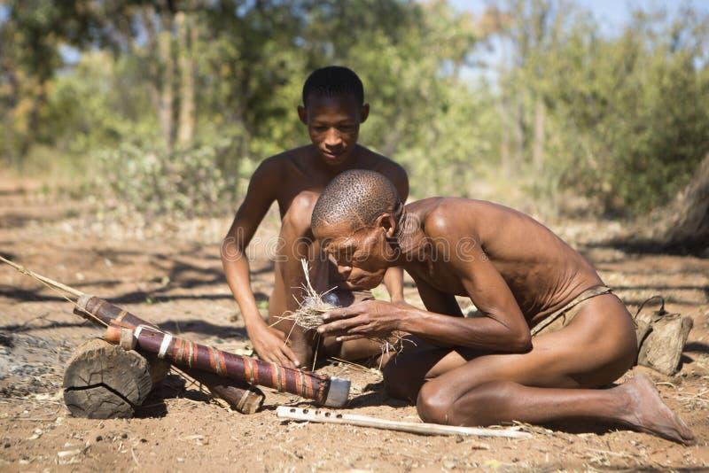 San-Buschmänner, die ein Feuer beginnen lizenzfreie stockfotografie