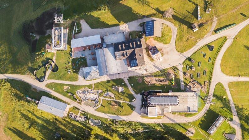 San Cassiano, Italien Lekplats, utomhus- idrottshall, barns mini- golf, restauranger och vattenlek på ankomsten av cablewayen royaltyfri foto