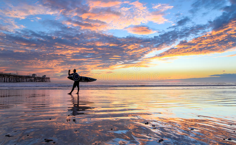 San Clemente Pier at Sunset. San Clemente Pier during a beautiful post-monsoonal storm sunset with surfer silhouette stock photo