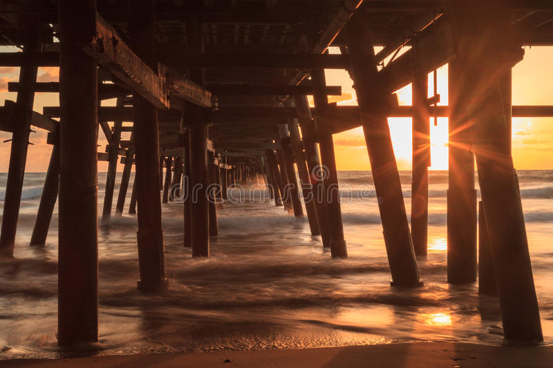 San Clemente pier at sunset in the fall. Under the San Clemente pier at sunset in the fall stock photo