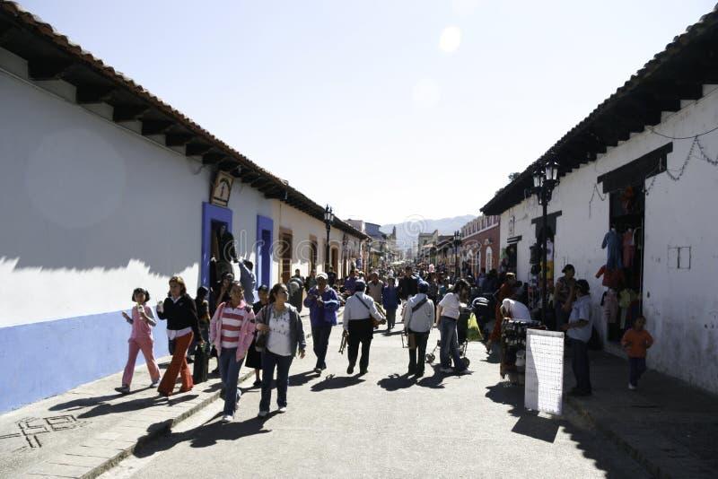 San Cristobal de Las Casas, Chiapas/México - 12-21-2008: Turistas que caminan abajo de la calle rodeada por las casas coloniales imagen de archivo