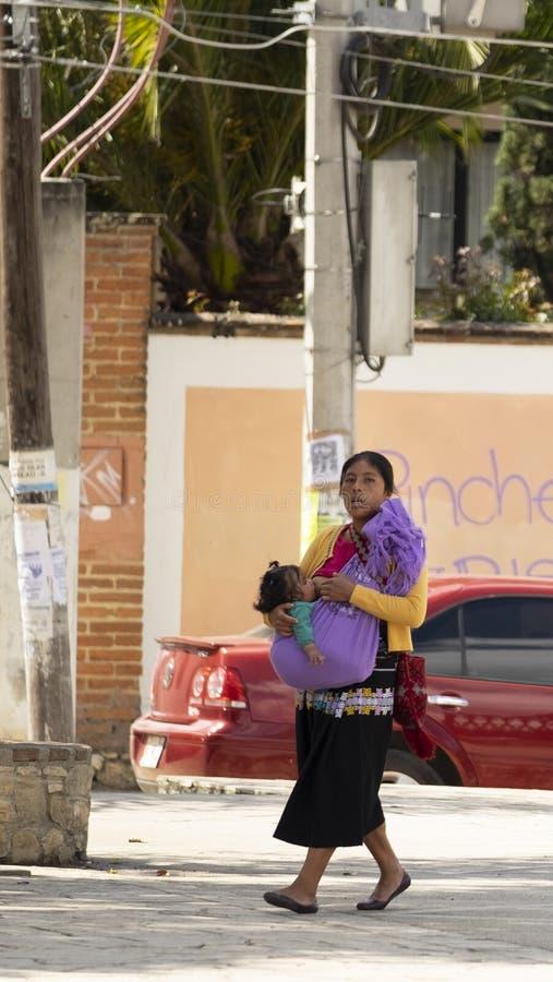 San Cristobal de las Casas, Chiapas, Mexico - March 7th, 2018: woman walking with baby on lap on the street royalty free stock photo