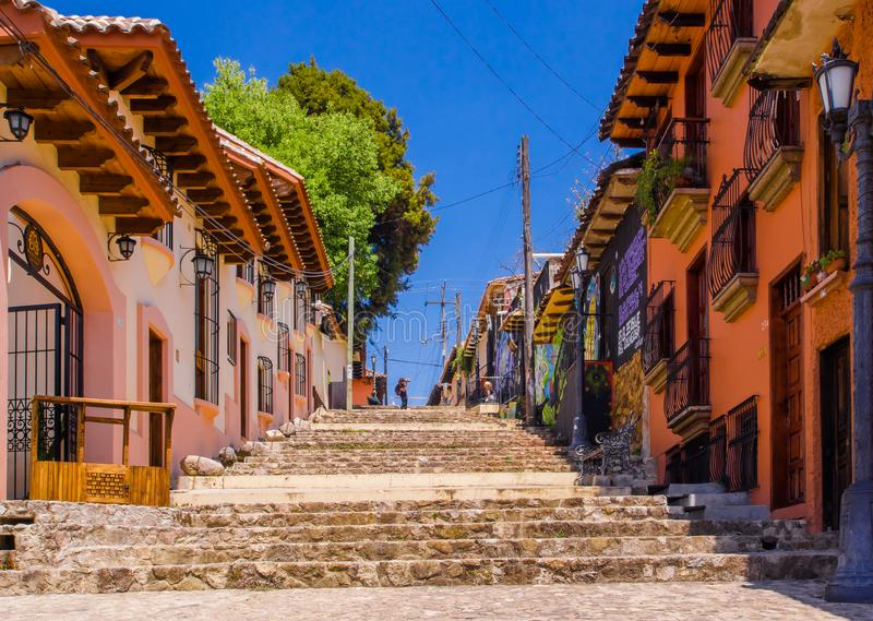 SAN CRISTOBAL DE LAS CASAS, MEXICO, MAY, 17, 2018: Outdoor view of teens walking to a hill with colorful steps in San royalty free stock photo