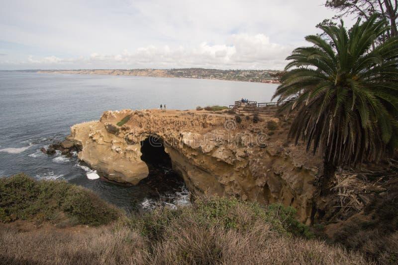 San Diego, Californië - Oktober 31,2016: Niet geïdentificeerde toerist bij een rotsachtig klippengebied in het Strand van La Joll stock foto