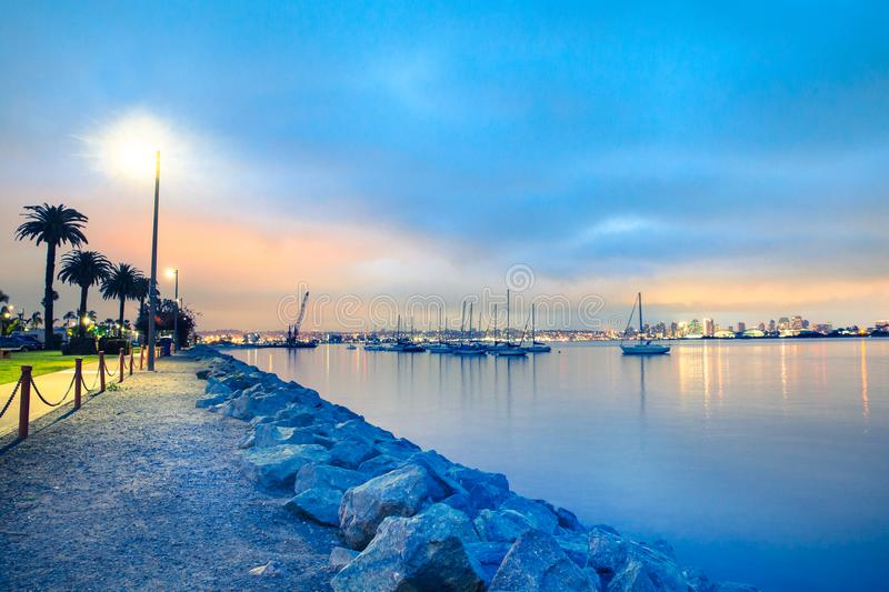 San Diego California evening scene with boats and skyline. View of San Diego California at sunset with boats and buildings seen across the water royalty free stock photography