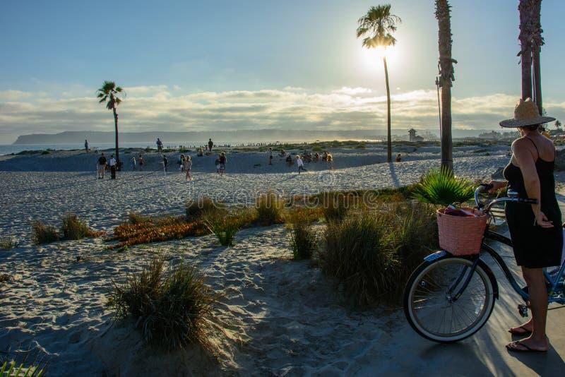 San Diego, California, los E.E.U.U. - 3 de julio de 2015: La hembra mira la puesta del sol en la playa de Coronado en San Diego fotos de archivo