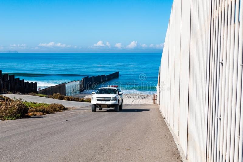 Border Patrol Vehicle Near End of Border Wall at Pacific Ocean. SAN DIEGO, CALIFORNIA - NOVEMBER 4, 2017: A Border Patrol vehicle patrols near the end of the stock photography