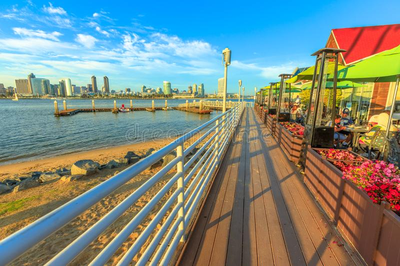 Bayside Village Pizzeria San Diego. San Diego, California, United States - August 1, 2018: wooden footpath walkway along Bayside Village Pizzeria with covered royalty free stock photo