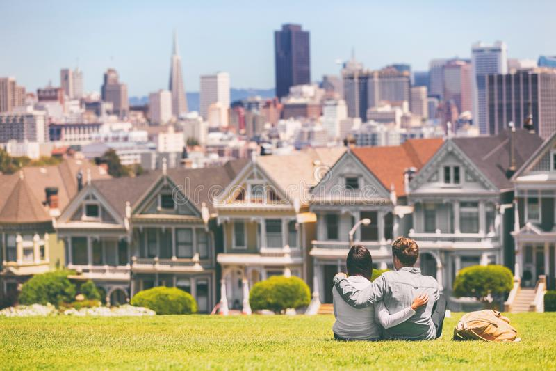 San Francisco - Alamo Square people. Couple tourists relaxing in Alamo Park by the Painted Ladies houses iconic landscape, The. Seven Sisters, San Francisco stock photo