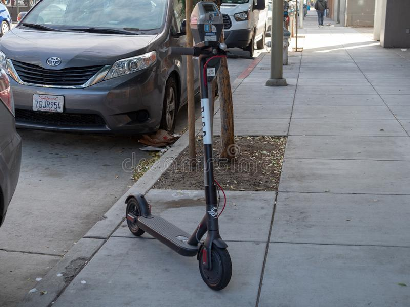 Bird, transportation start up, electric scouter parked on sidewalk stock image