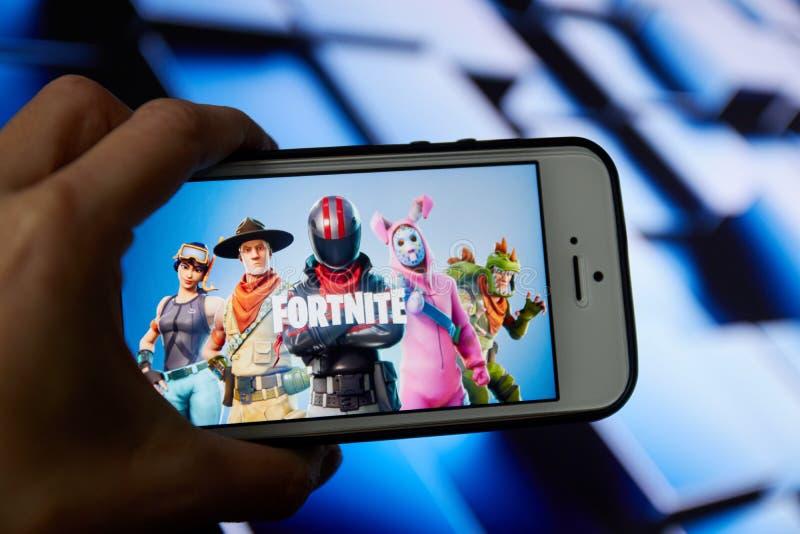 San Francisco, CA de V.S. - April 2019: hand die een telefoon met een Fortnite-spel dicht houden omhoog embleem stock foto's