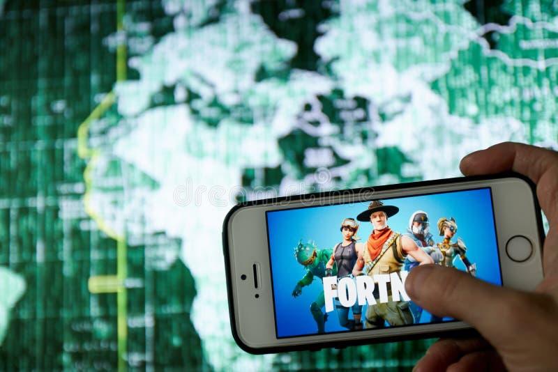 San Francisco, CA los E.E.U.U. - abril de 2019: mano que sostiene un tel?fono con un cierre del logotipo del juego de Fortnite pa fotos de archivo