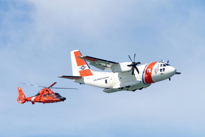 Coast Guard helicopter and plane flying in air show stock photo