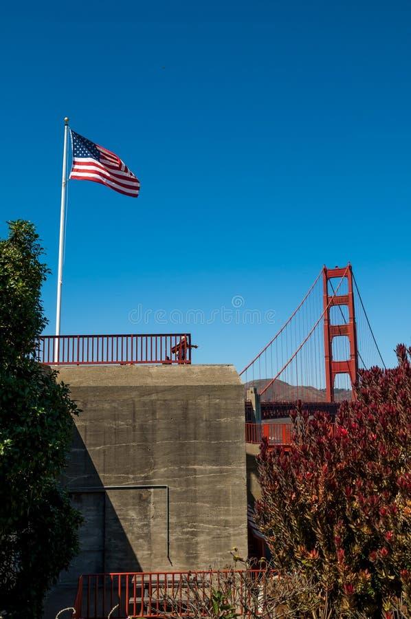 SAN FRANCISCO, CALIFÓRNIA - 8 de setembro de 2015 - o voo da bandeira americana no vento com golden gate bridge e céu azul brilha imagens de stock