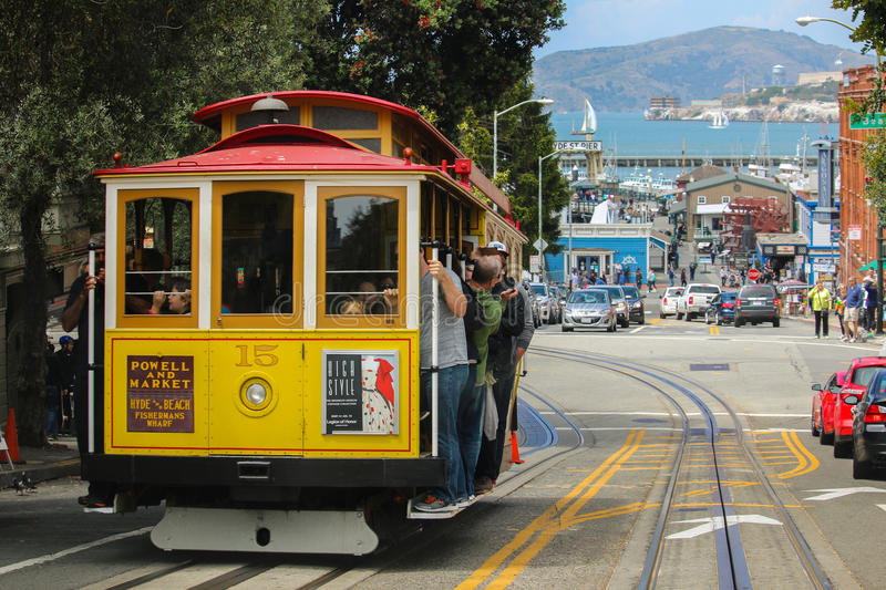 San Francisco, California - Mai 23, 2015: Tourists riding on the iconic cable car, blue sky day at top of Hyde Street view stock image