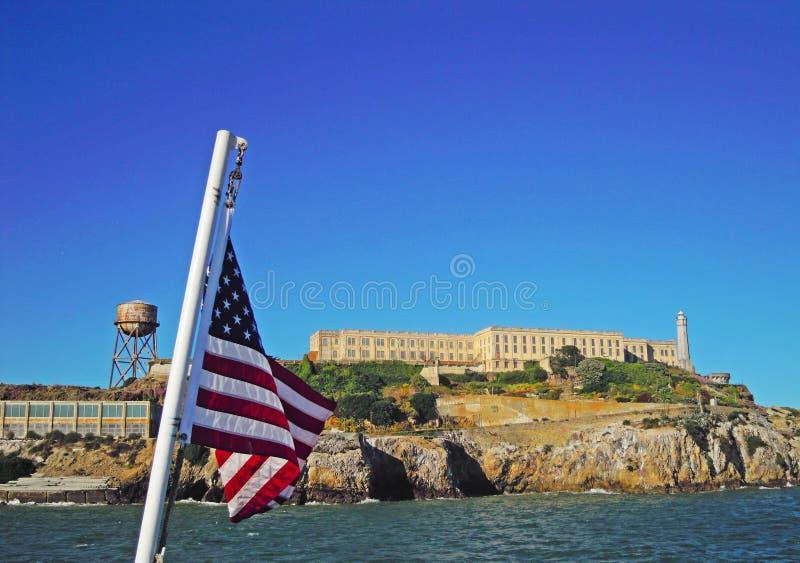 San Francisco, California, United States of America, Usa. Usa waving flag and Alcatraz island, skyline and the Bay on 7 June 2010. Alcatraz island, part of royalty free stock images