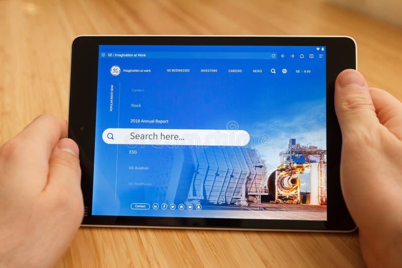 SAN FRANCISCO, de V.S. - 1 April 2019: Sluit tot handen houdend tablet gebruikend Internet en kijkend door GE-website, in San stock afbeelding