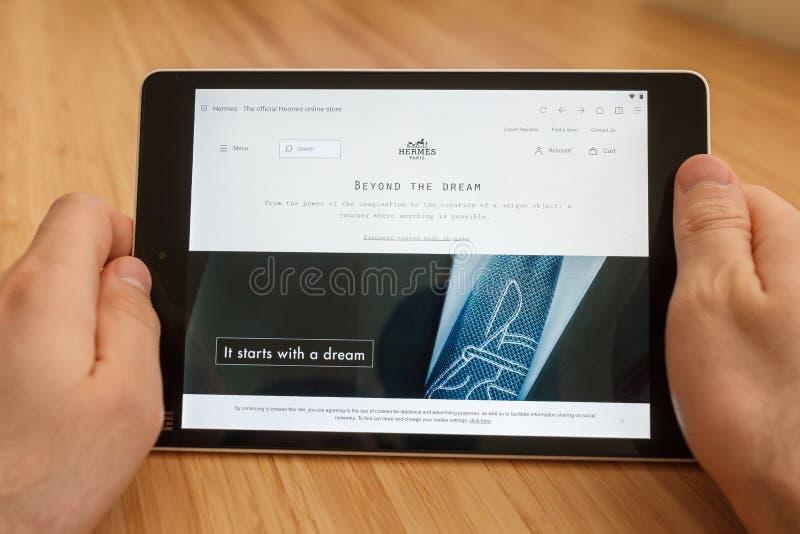 SAN FRANCISCO, de V.S. - 1 April 2019: Sluit tot handen houdend tablet gebruikend Internet en kijkend door Hermes-website, in San royalty-vrije stock foto