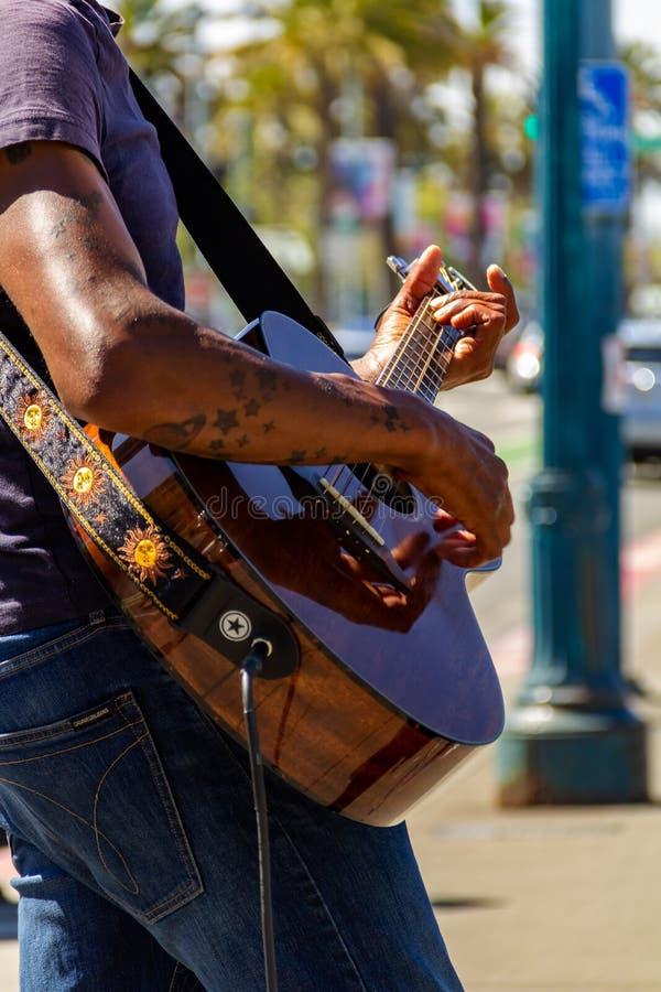 San Francisco, de V.S. - Juli 15, 2019, mannelijke handen en vingers van een gitarist dat de koorden op een bruin koord 6 raken royalty-vrije stock foto's