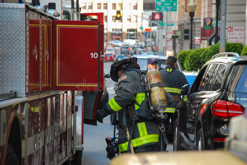 San Francisco Fire Engine and Firemean loading up. Action of a San Francisco Fireman at in front of a hotel , loading or unloading gear , full dressed in fire royalty free stock photos