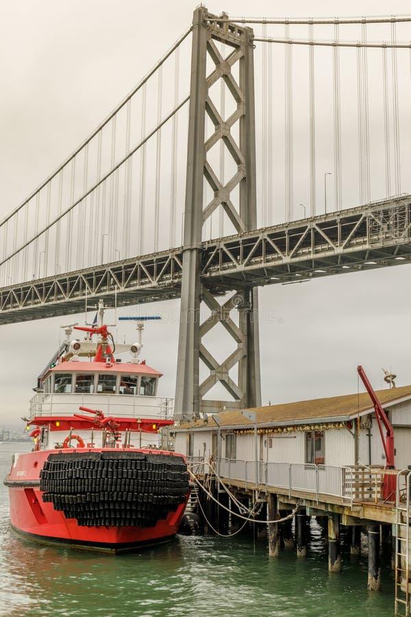 San Francisco Fireboat machte mit der Bucht-Brücke im Hintergrund fest stockfotografie