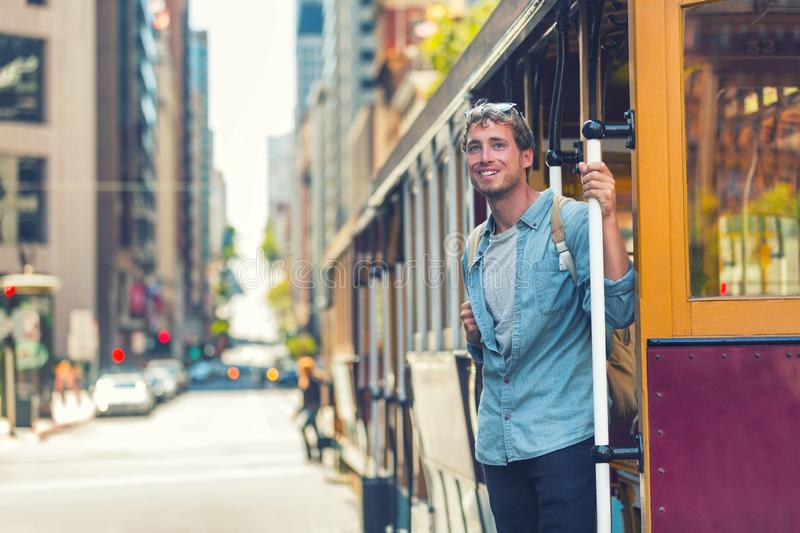 San Francisco hipster man taking public cable car transport for tourism travel. University student with bag morning commute in stock photo