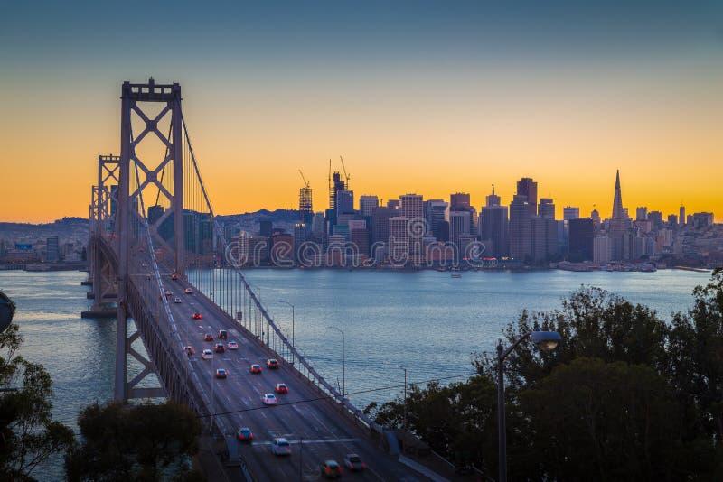 San Francisco horisont med den Oakland fjärdbron i skymning, Calif arkivbild