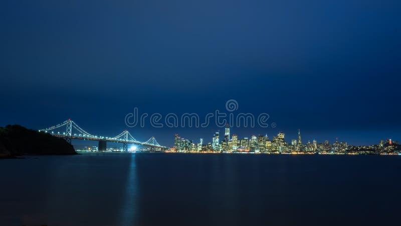 San Francisco horisont på natten med fjärdbron fotografering för bildbyråer