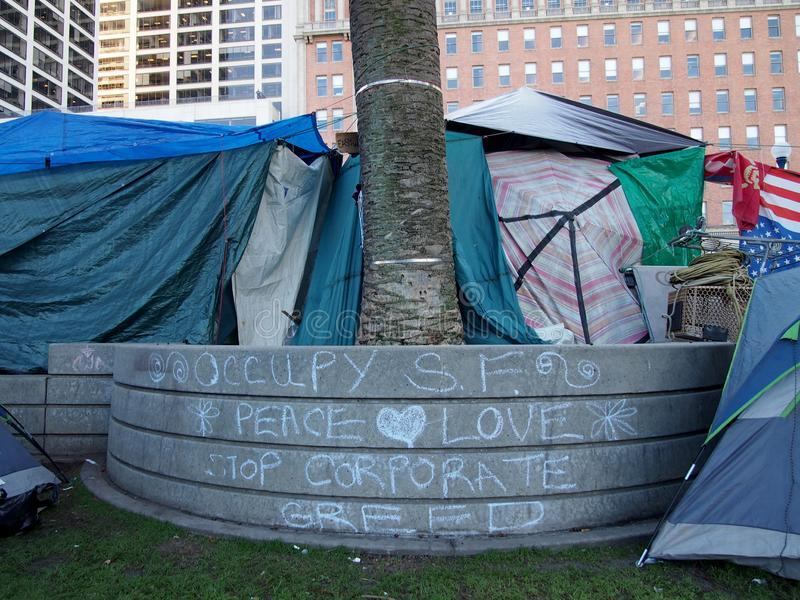Tents surround wall with the writing of Occupy SF, Peace, Love, Stop Corporate Greed in Chalk stock image