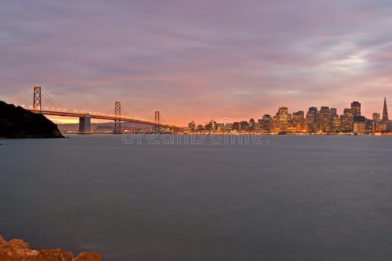 San Francisco och fjärden överbryggar på natten arkivbild