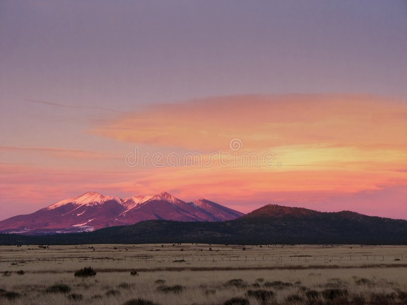 San Francisco Peaks alpenglow. The San Francisco Peaks and lenticular clouds in Arizona lit by evening alpenglow royalty free stock photo
