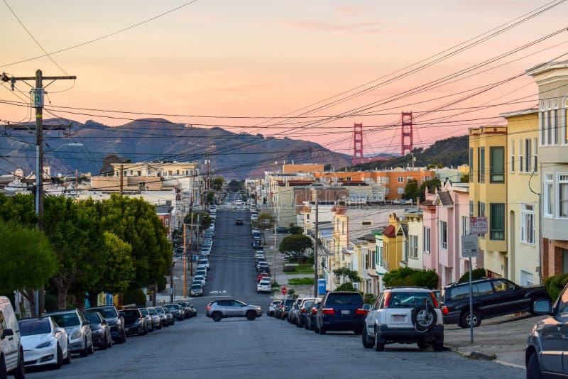 San Francisco Skyline com vizinhança residencial, a rua curvada e golden gate bridge no por do sol imagens de stock royalty free