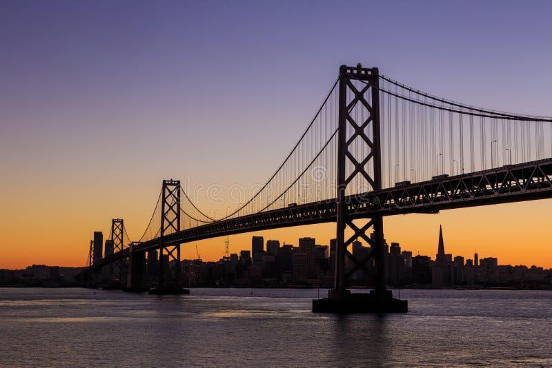 San Francisco-Skyline und Bucht-Brücke bei Sonnenuntergang, Kalifornien lizenzfreie stockbilder