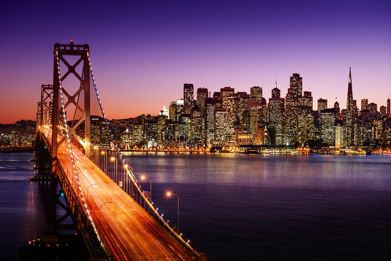 San Francisco-Skyline und Bucht-Brücke bei Sonnenuntergang, Kalifornien lizenzfreie stockfotos