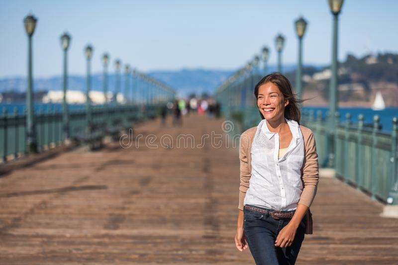 San Francisco travel lifestyle woman walking happy on pier. Asian girl smiling relaxing in harbor city stock photo