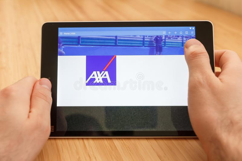 SAN FRANCISCO, US - 1 April 2019: Close up to hands holding tablet using internet and looking through AXA web site, in San. Francisco, California, USA. An royalty free stock images